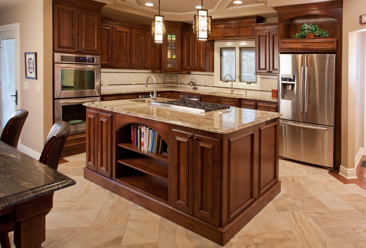 Example of home remodeling design featuring a high-end kitchen with a large marble and wood island
