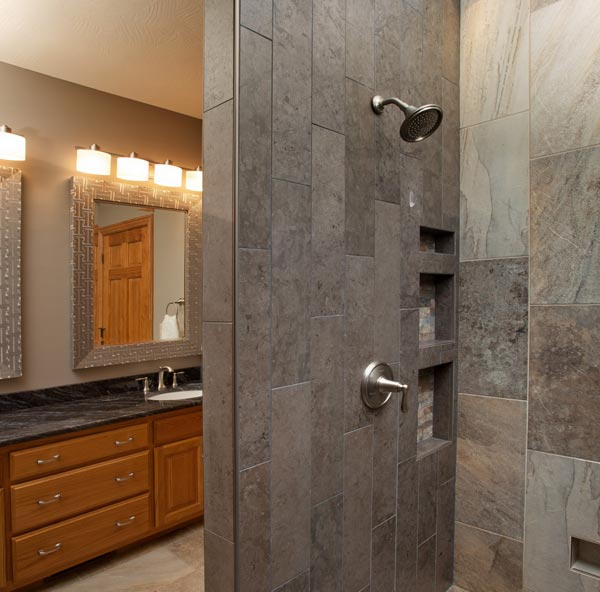 A modern luxury bathroom design with a tile shower and sink
