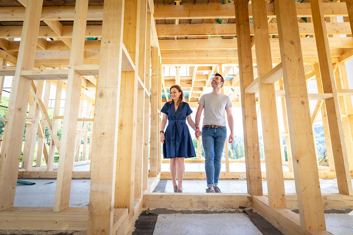 A loving husband and wife holding hands walking through the construction site of their new home