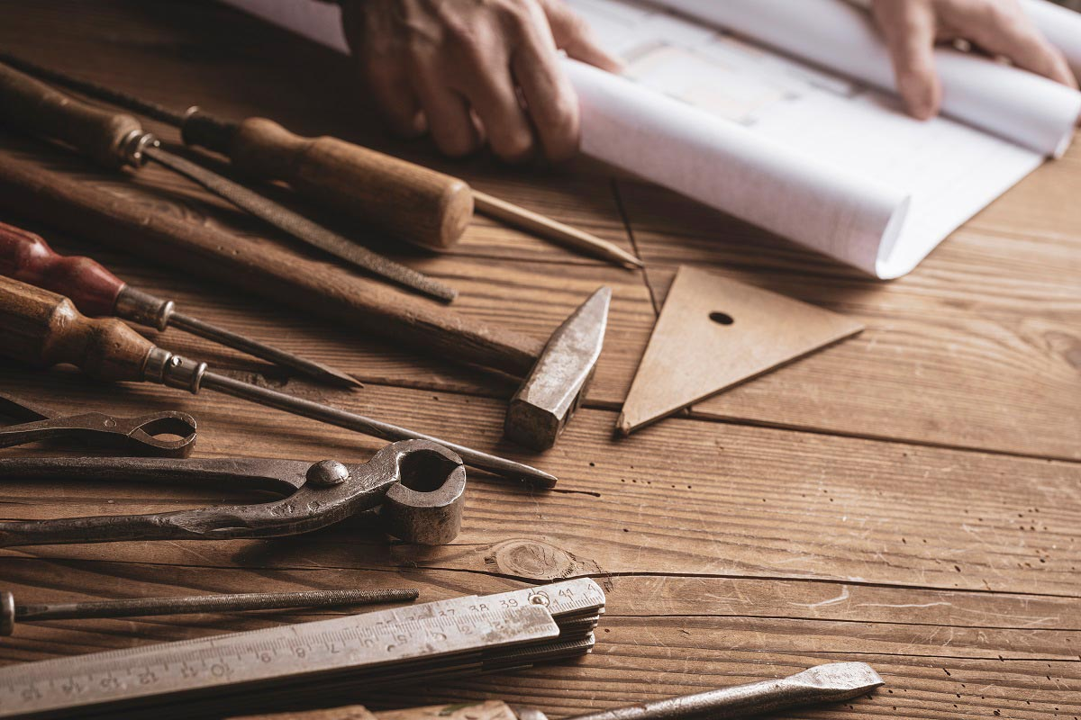 A man unrolling blue prints next to woodworking tools on a wooden surface