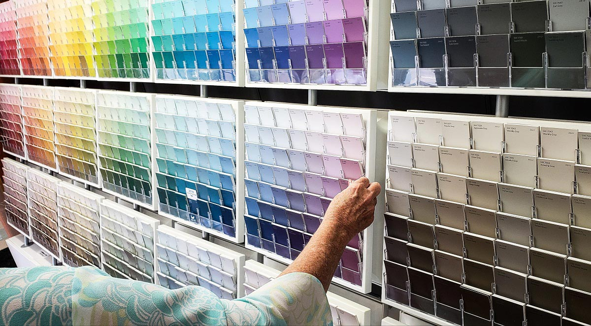 A woman choosing from a selection of paint swatches